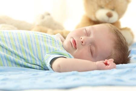 Portret van een enkele baby slapen op een bed Stockfoto