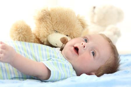 Happy baby and teddy bear lying on a bed