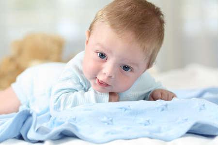 Portrait eines süßen Schätzchens, das Sie auf einer blauen Decke in einem Bett betrachtet Standard-Bild - 83953341