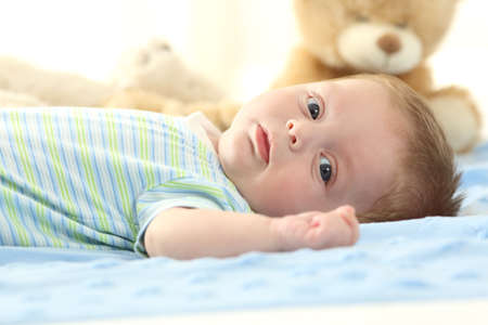 Portrait of a baby lying on a bed and looking at you