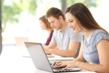 教室でノート パソコンを持つ行を検索する真面目な学生の側面図