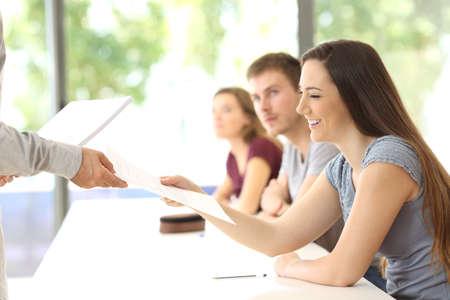 De student krijgt een examen van de docent in een klaslokaal
