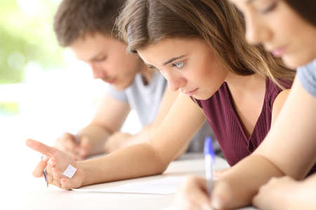 Bad student reading a cheating sheet during an exam in a classroom