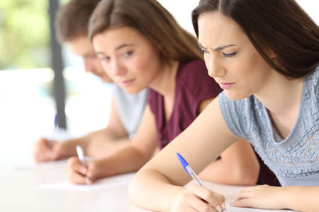 Student trying to copy an exam from another classmate at classroom Stock Photo