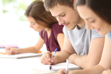 Close up of three students studying taking notes at classroom