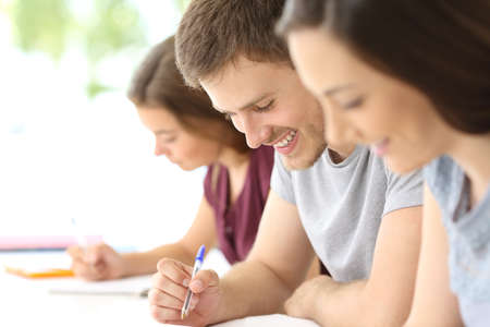 Zblízka šťastného studenta s poznámkami ve třídě Reklamní fotografie