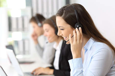 Happy teleoperator working at call center with other employees in the background Stockfoto