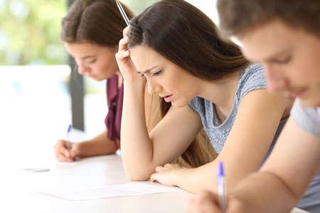 Zijaanzicht van een ongerust gemaakte student die een moeilijk examen in een klaslokaal probeert te doen