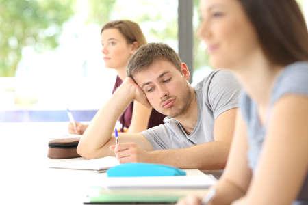 Tudiant ennuyé distrait pendant une classe dans la salle de classe avec des camarades de classe en arrière-plan Banque d'images - 84001749