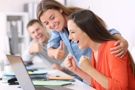 Gelukkige medewerker wordt gefeliciteerd door collega's na succes op kantoor Stockfoto
