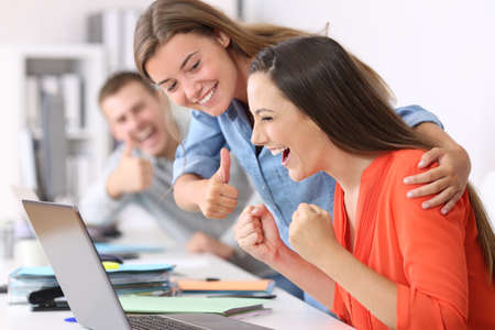 Happy employee being congratulated by colleagues after success at office 版權商用圖片