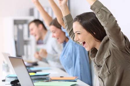 Tres empleados emocionados recibiendo buenas noticias en línea en sus portátiles en la oficina Foto de archivo - 84001756