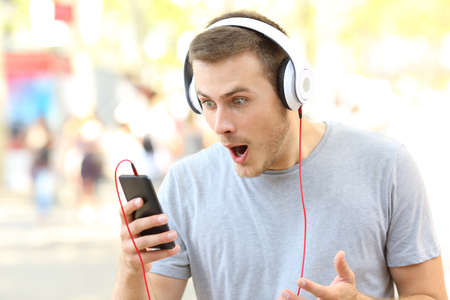 Surprised guy receiving shocking news on a smart phone on the street
