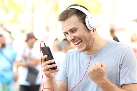 Opgewonden kerel die goed nieuws ontvangt op een mobiele telefoon op straat