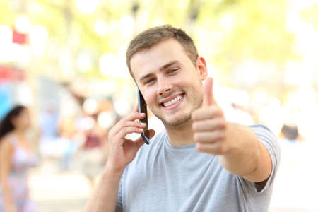 Front view portrait of a guy calling on phone looking at you with thumbs up on the street Фото со стока