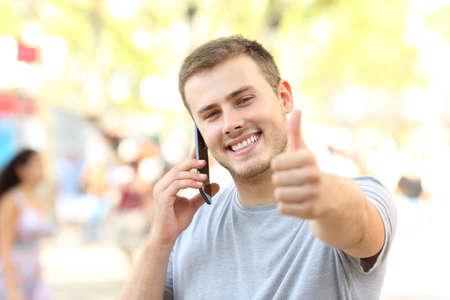 Vooraanzichtportret van een kerel die telefoon uitnodigen die u met duimen omhoog op de straat bekijken