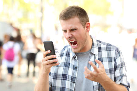 Angry man holding crashed mobile phone on the street Stockfoto