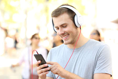 Happy boy listening to music and selecting a song walking on the street Stock Photo