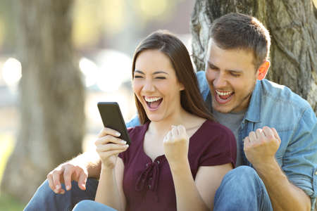 Excited couple reading good news in a smart phone sitting in a park Archivio Fotografico