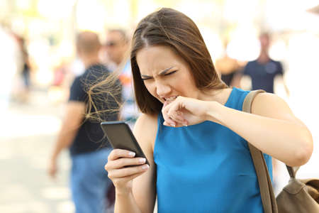 Angry woman fed up of her mobile phone on the street