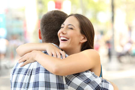 Gelukkige paar of vrienden knuffelen na een ontmoeting op straat