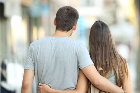 Back view portrait of a casual couple walking together on the street