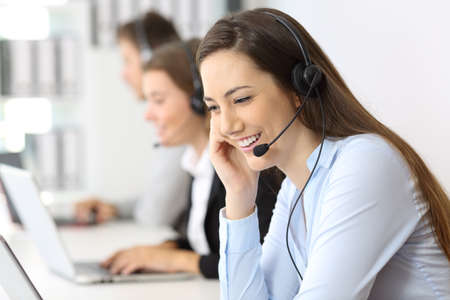 Telemarketing operator talking working at office with other workers in the background