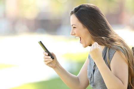 Profile of a single excited woman using a smart phone outdoors in the street