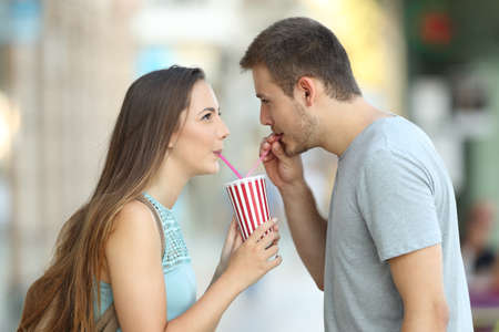 Side view portrait of a happy couple sharing a takeaway refreshment in the street Imagens