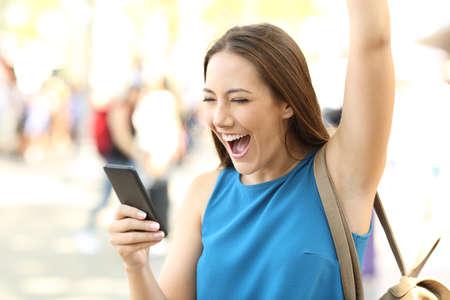Excited mujer levantando brazo recibiendo buenas noticias en un teléfono móvil en la calle Foto de archivo - 83997384