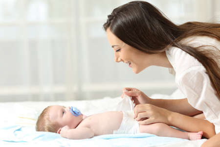 Vista lateral retrato de una madre feliz cambio de pañales a su bebé Foto de archivo - 83997393