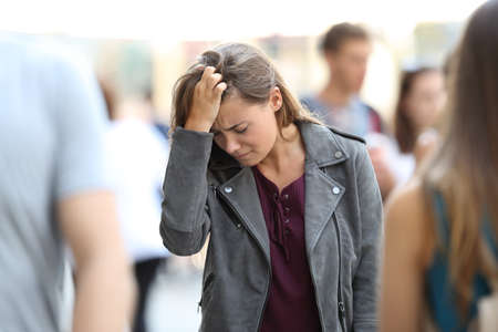 Depressed teen feeling lonely walking on the street surrounded by people