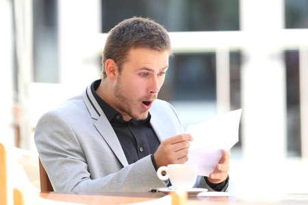Ritratto di un dirigente stupito che legge una lettera che si siede in una caffetteria Archivio Fotografico - 84149581