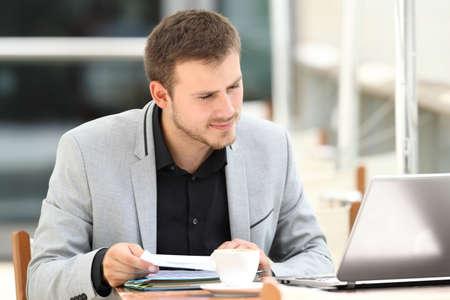 Ejecutivo comparando documentos en línea con un ordenador portátil sentado en una cafetería Foto de archivo