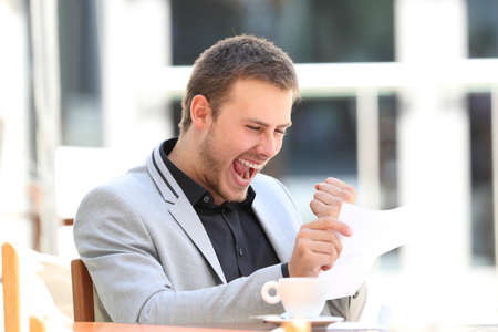 Opgewonden executive lezen een brief in een koffiewinkel Stockfoto