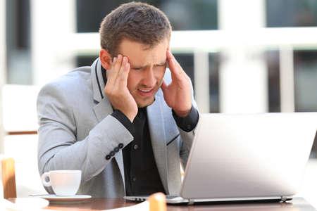 Vermoeide uitvoerende lijdende hoofdpijn aan het werk zittend in een koffiewinkel