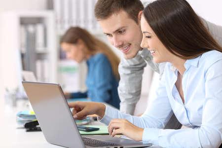 Twee gelukkige collega's coorking online samen met laptop op kantoor