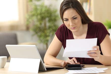 Aandachtige vrouw het berekenen boekhoudingzitting in een bureau thuis