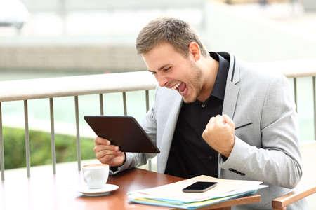 Opgewekte stafmedewerker die goed nieuws online zittend in een koffiewinkel ontvangt