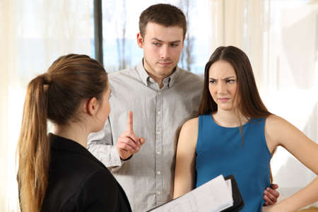 Bad real estate agent attending to discontent customers in a house interior