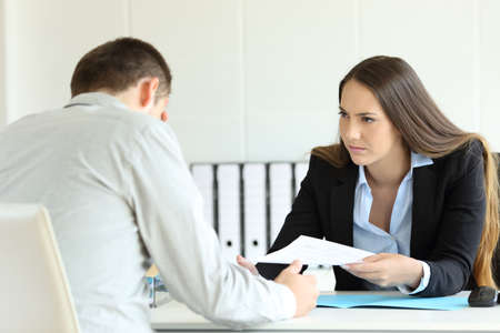 Boze baas die een document geeft aan een verdrietige werknemer die in een bureau op kantoor zit