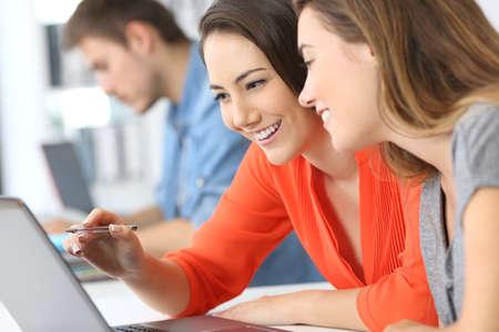 Due dipendenti collaborano in linea con un computer portatile in ufficio