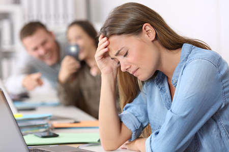Sad cyber bullying victim being photographed by her colleagues at office Stock Photo