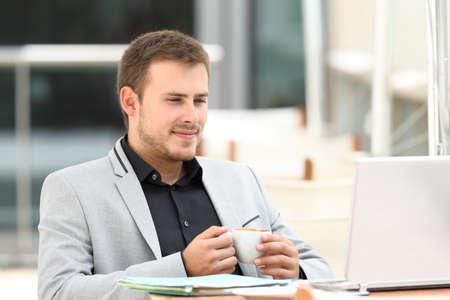 Ejecutivo de lectura en línea de contenido en un ordenador portátil sentado en una cafetería Foto de archivo - 84207903