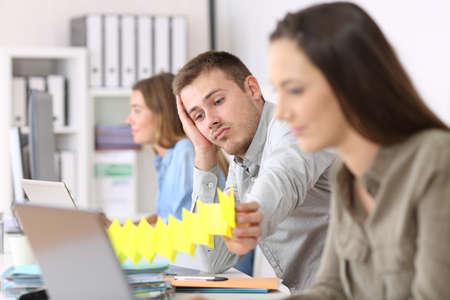 事務所の他の労働者間のデスクトップに座って退屈な怠惰な従業員の肖像画