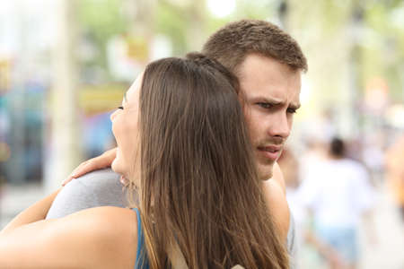 Discontent boyfriend hugging his partner on the street