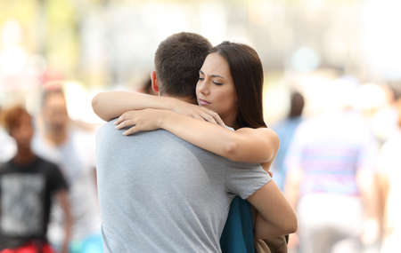 Discontent woman hugging her couple with problems on the street Standard-Bild