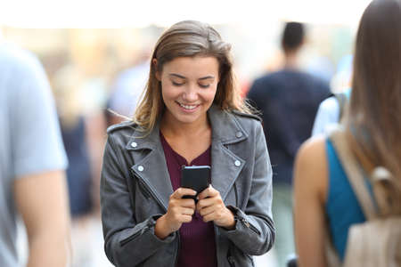 Front view of a happy teen chatting on smart phone surrounding by people on the street