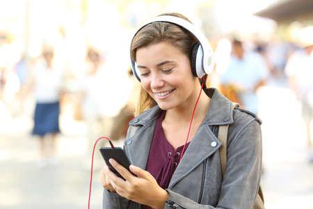 Happy teenager listening music wearing headphones on the street Stock Photo