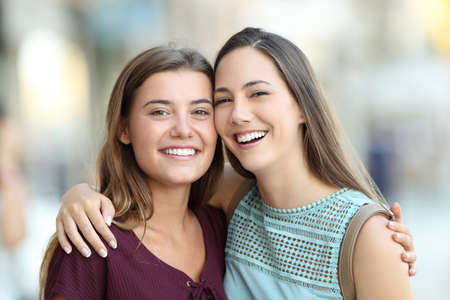 Two friends posing with perfect smiles and looking at camera on the street